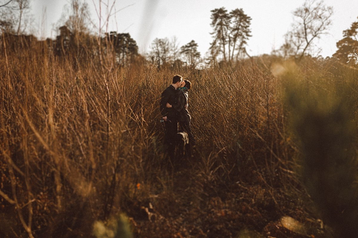 Couple kissing standing in thick trees, Engagement Shoot London