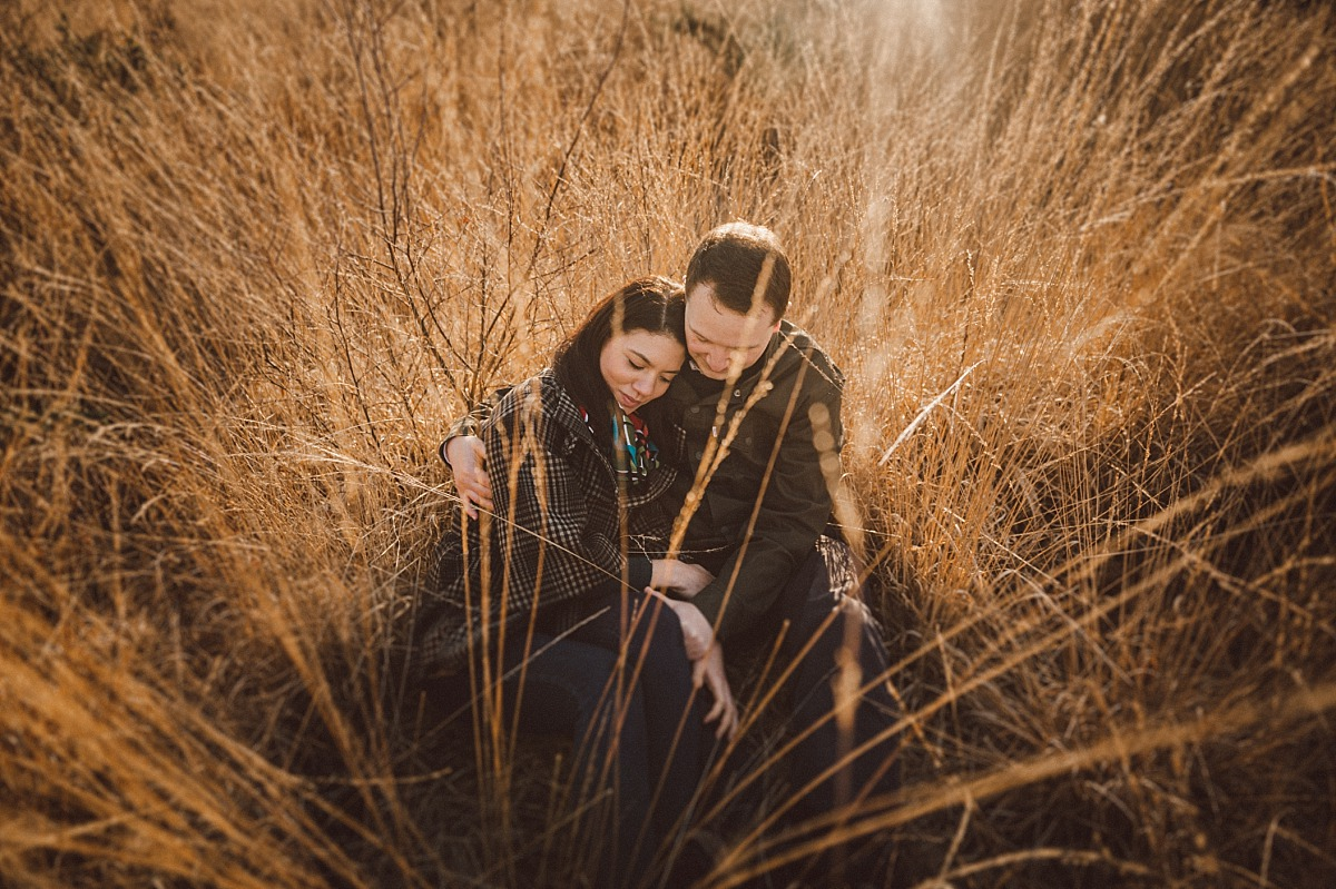 Photo of couple in love sitting in long grass