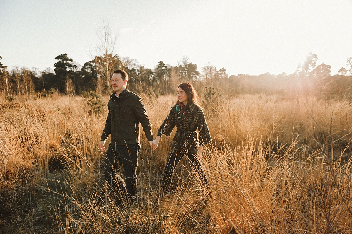 Photo of couple walking through long grass