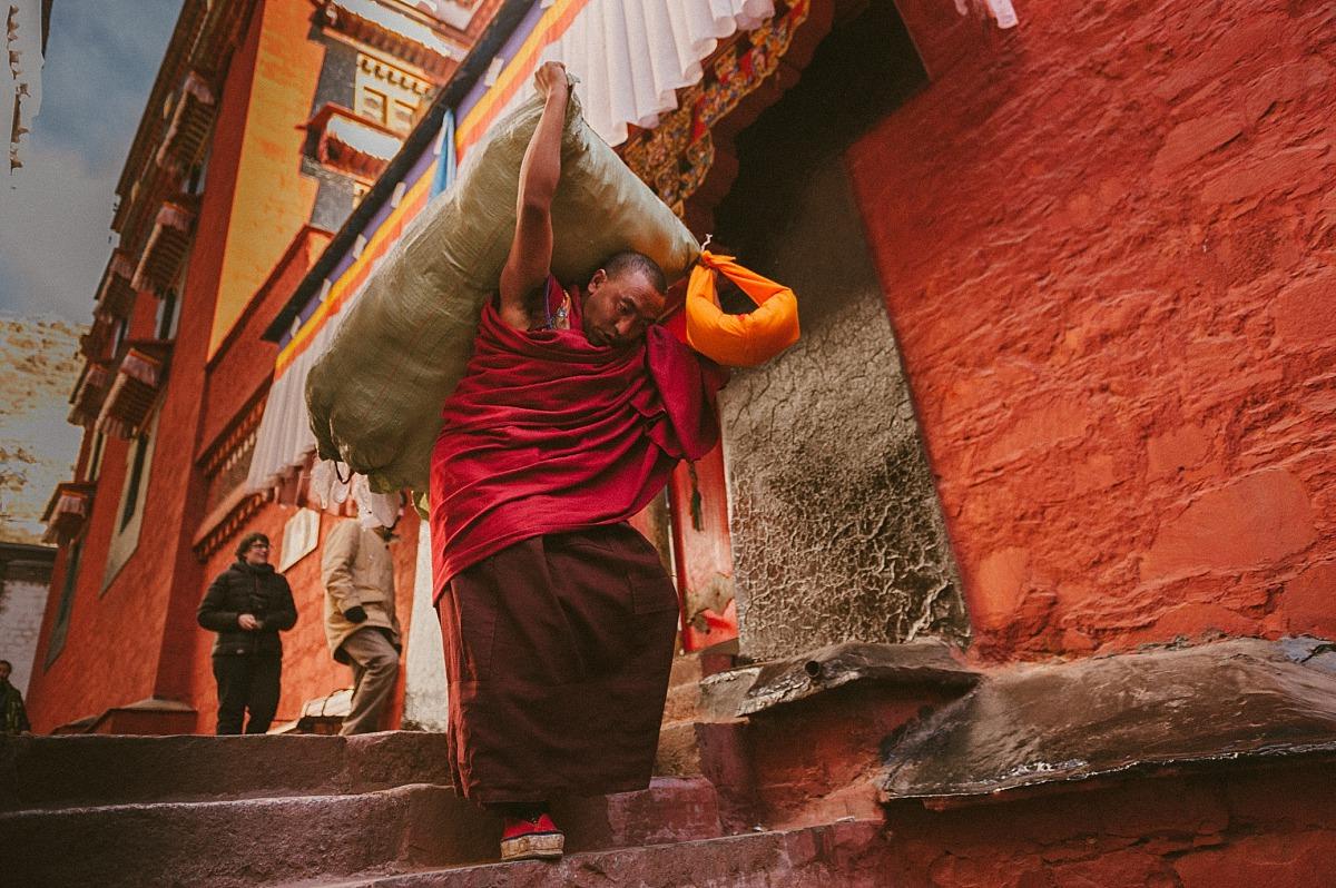Tibetan monk carrying sack