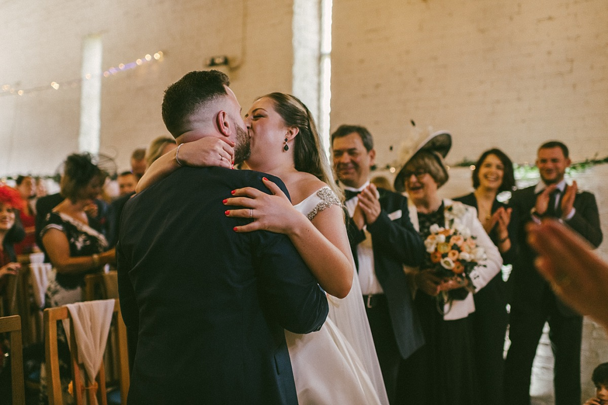 Wedding photo of Bride & Groom kissing in barn at Ufton Court