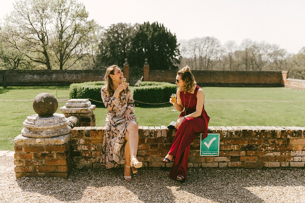 Two female wedding guests sitting on wall
