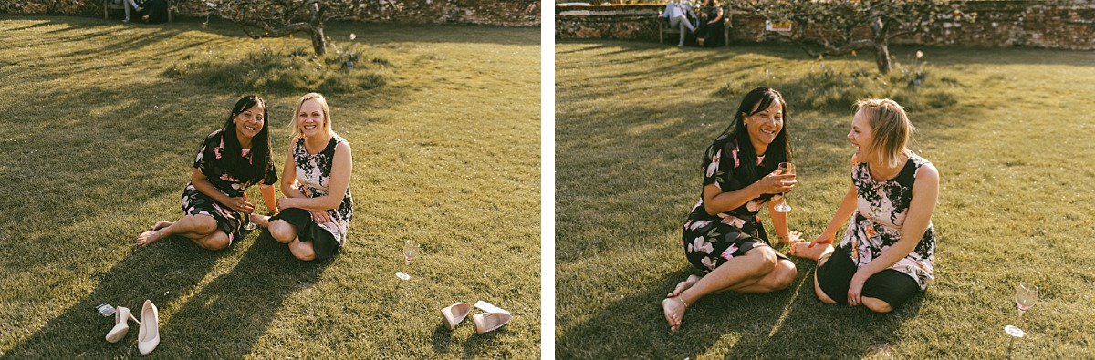 Female wedding guests sitting on grass, by Reading wedding photographer