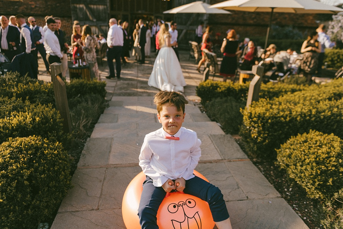 Young boy at wedding playing on a Space Hopper