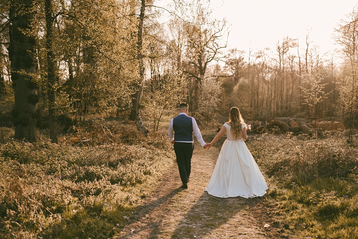 Bride & Groom walking into forest on Summer evening
