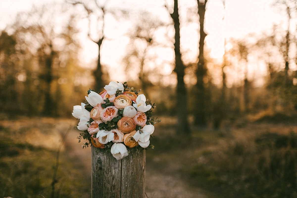 Photo of Bridal bouquet sitting on top of wooden pillar