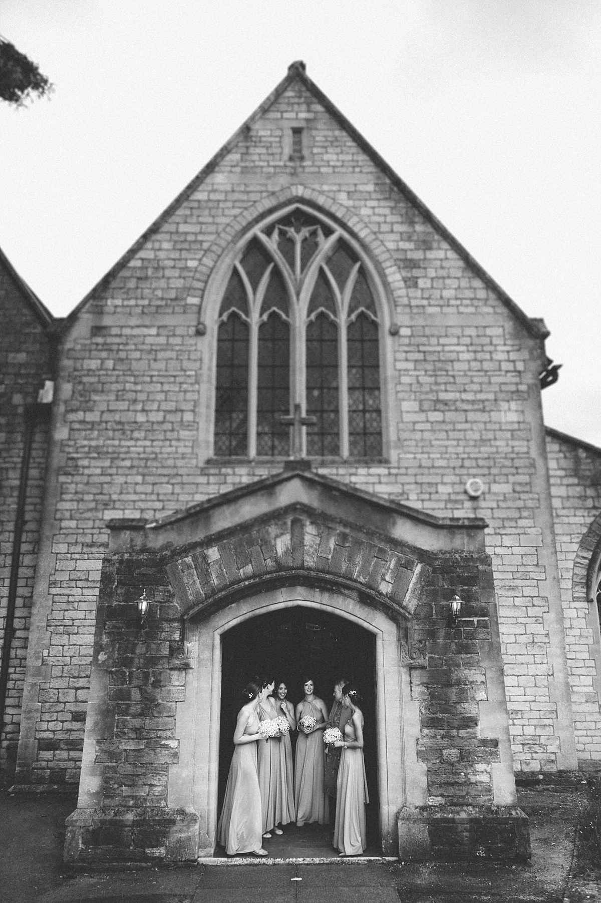 black & white photo of bridesmaids hiding from rain