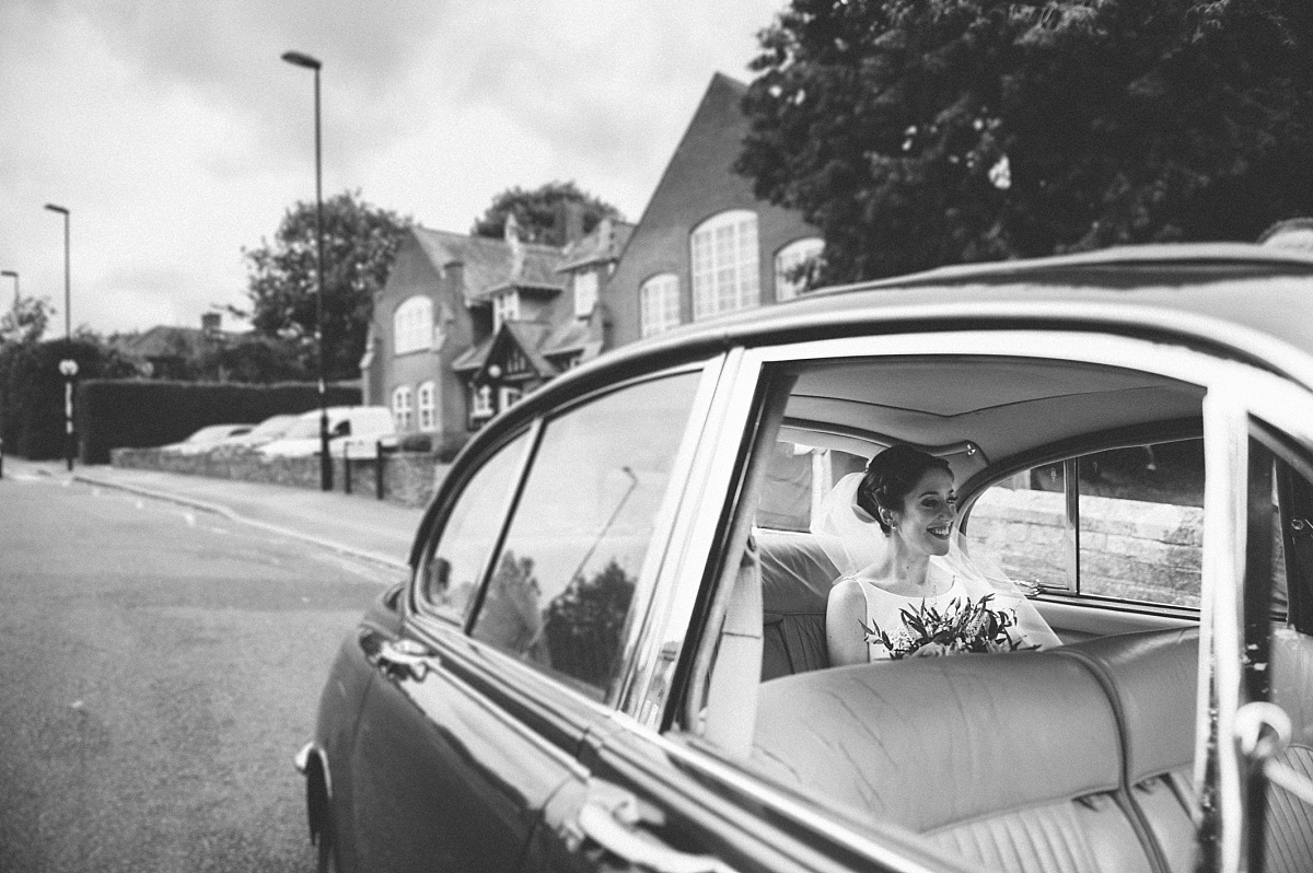 black & white photo of brides in classic car