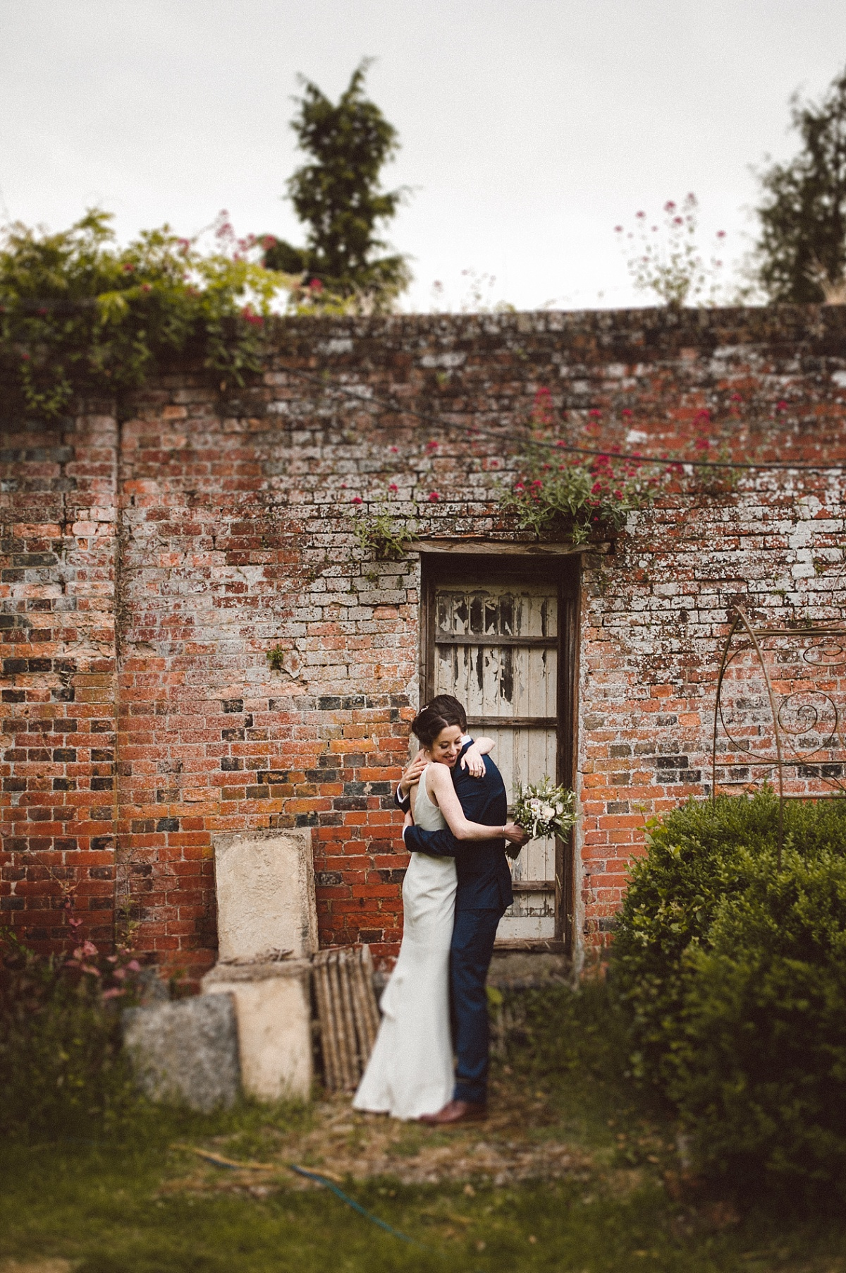 photo of couple infront of rustic wall