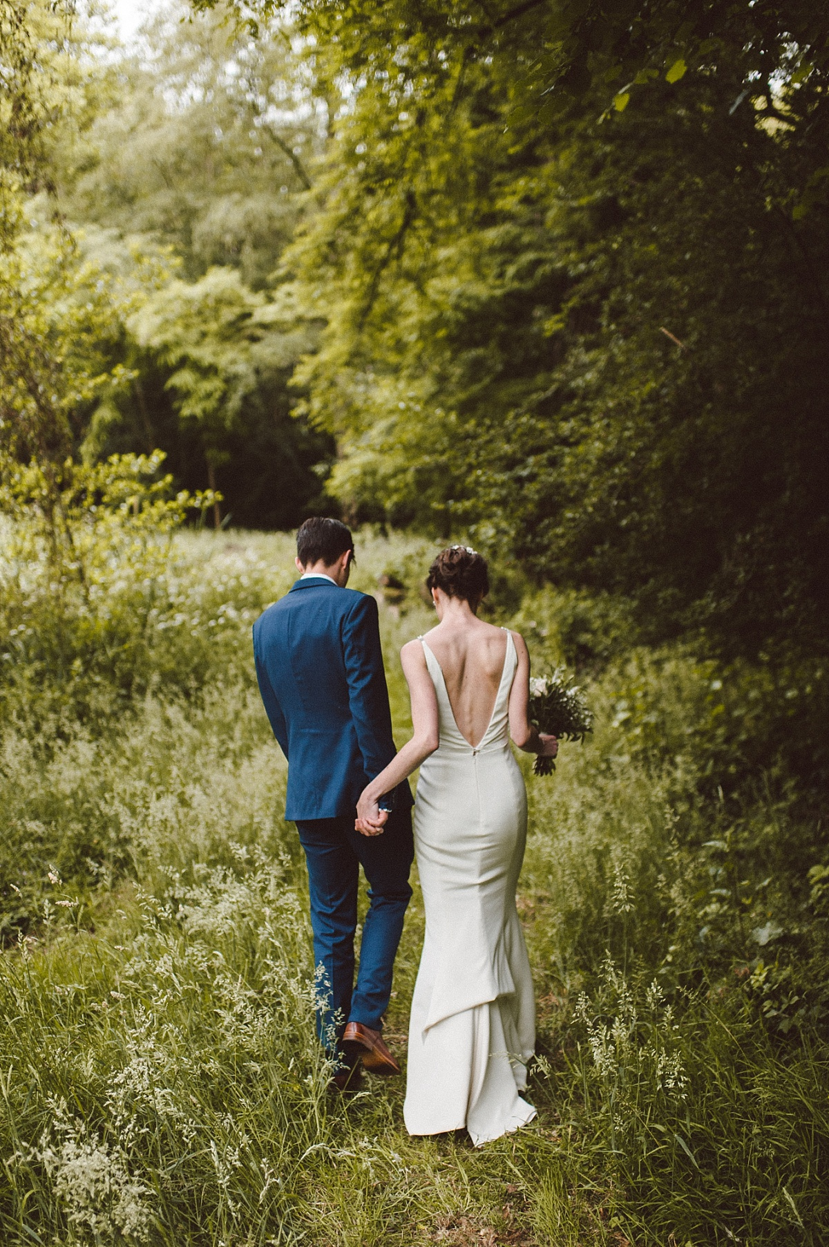 couple by lake on their wedding day