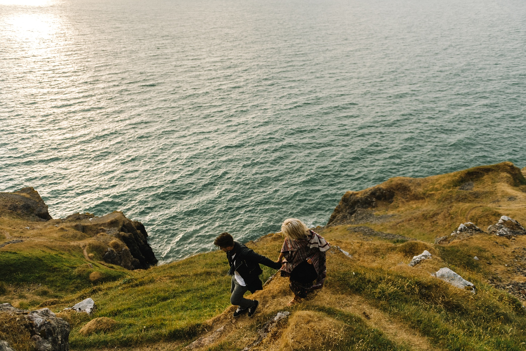 Couple walking along cliff top path by South Wales wedding photographer
