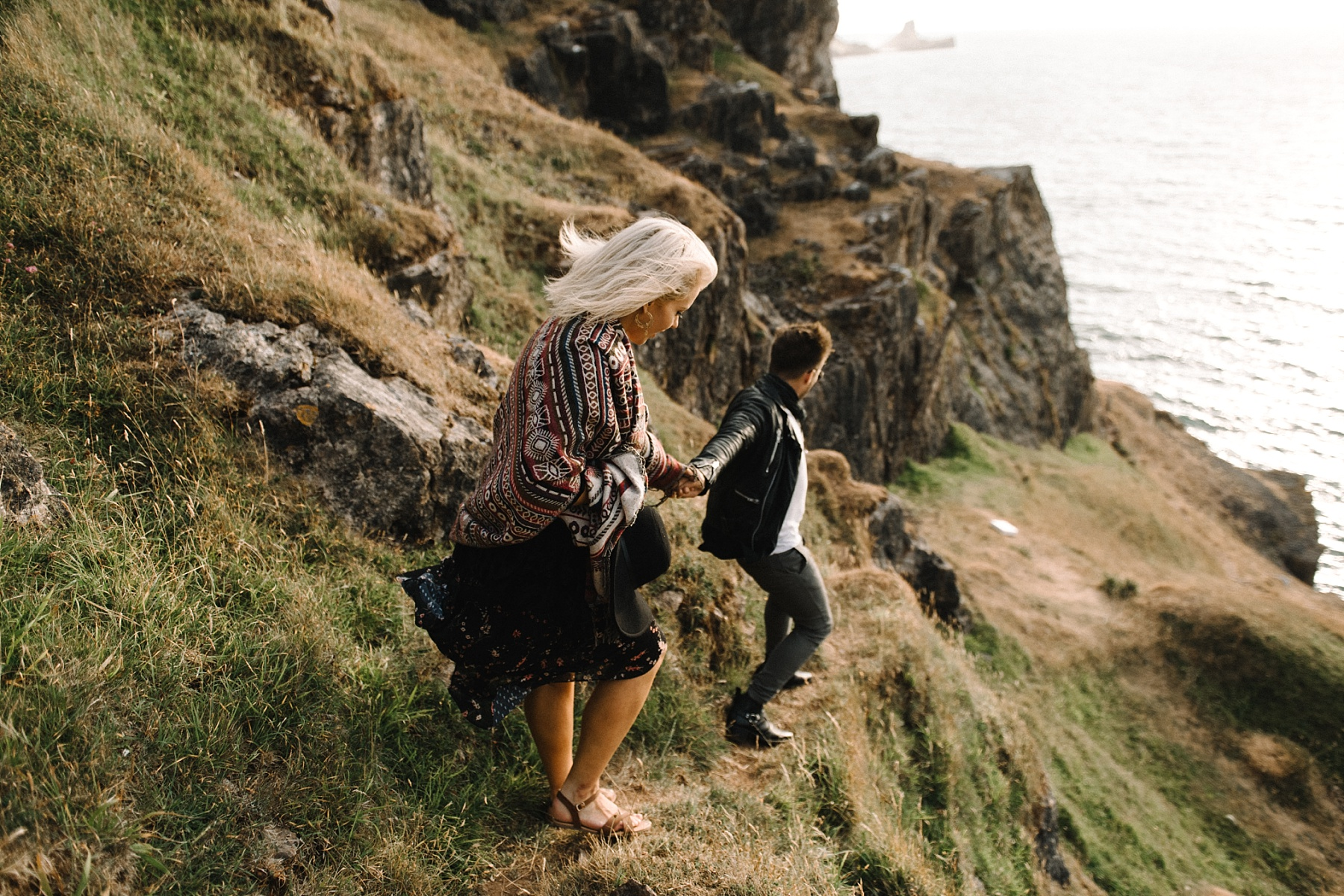 couple walking down steep cliff
