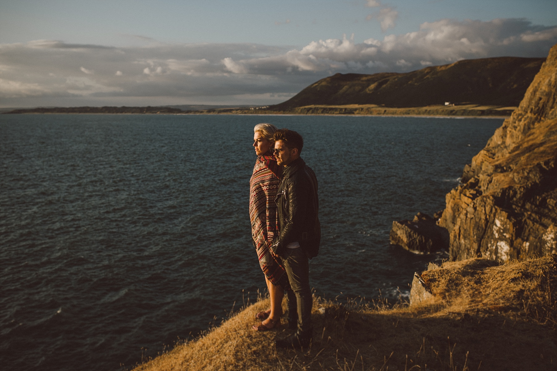 Couple looking out to sea with cliffs behind