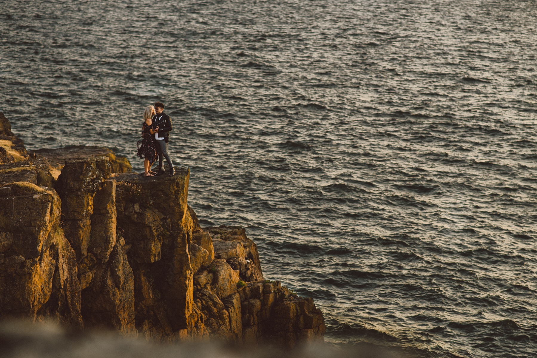 couple kissing on top of cliff