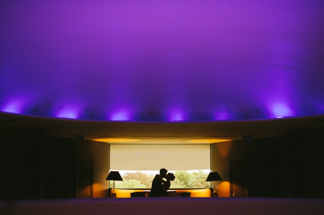 Groom kissing bride with purple lights on ceiling
