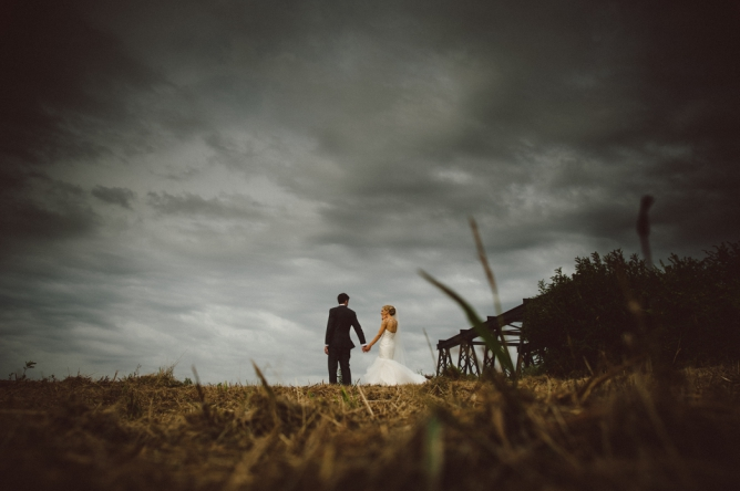 Photo of Bride & Groom walking under dark clouds