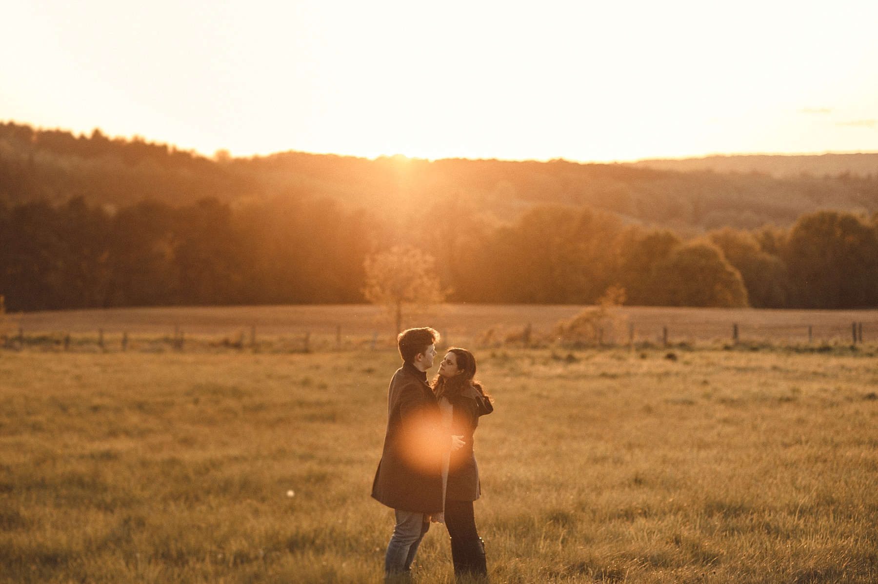 Photograph of couple standing in field in the hills